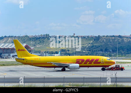 Cargo aircraft -Boeing 737-, of -Air Ghana DHL- airline, being towed by a tug tractor, in Madrid airport. - Stock Photo
