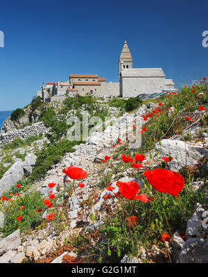 The hilly Lubenice town on the Island of Cres with poppy flowers in the front - Stock Photo