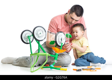 kid boy and his daddy fixing children bike - Stock Photo