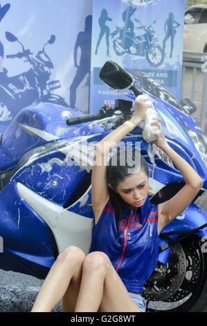 Beautiful woman posing in suzuki motorcycle when photo contest in automotive event tumplek blek 2016, Jakarta, Indonesia - Stock Photo