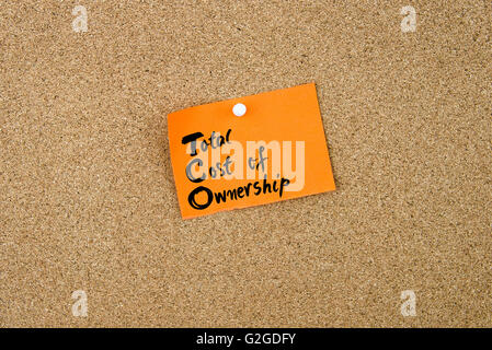 Business Acronym TCO as Total Cost Of Ownership written on orange paper note pinned on cork board with white thumbtacks, - Stock Photo