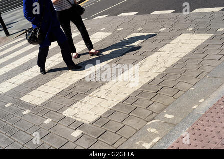 People using a pedestrian crossing in Chelmsford, Essex, England with just legs and feet visible, no faces. - Stock Photo