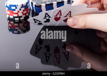 Woman holds aces poker cards with reflection and casino chips in the background - Stock Photo