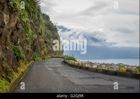 Old mountain road between mountains and ocean at Madeira island. - Stock Photo