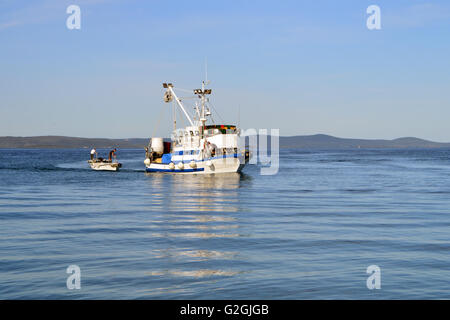 Fishing boats with fishermen in calm blue sea - Stock Photo