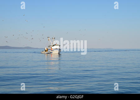 Fishing boat with fishermen in calm blue sea - Stock Photo