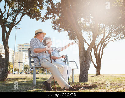 Outdoor shot of a senior couple sitting on a park bench with woman showing something interesting to her  husband. - Stock Photo