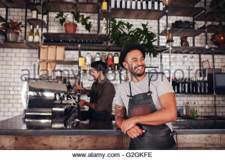 Portrait of cafe owner wearing a hat and apron standing at the counter and looking away. Barista working in background - Stock Photo