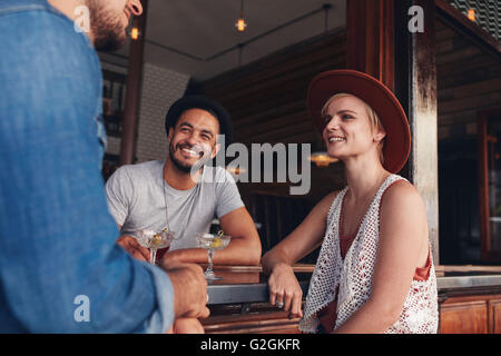 Group of young friends sitting and talking at a cafe. Young men and women meeting in a coffee shop. - Stock Photo