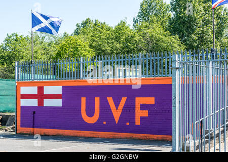 Large UVF mural in loyalist Sydenham area of East Belfast with Scotland's national flag flying overhead. - Stock Photo