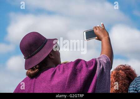 A spectator wearing a hat at the Lowveld Airshow taking a video with her cell phone - Stock Photo