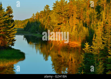 Sun setting on water at Reed Narrows, connected to Lake of the Woods, Reed Narrows, Ontario Canada - Stock Photo