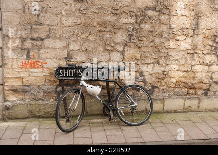 single bike chained up to steel signpost of ship street creating a trip hazard - Stock Photo