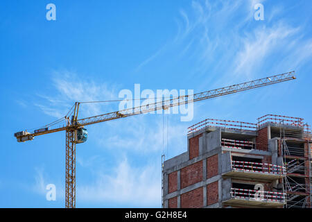 Building Crane and Building Under Construction, on blue sky background - Stock Photo