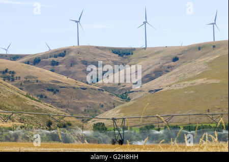 Wind turbines on top of hill, with rolling irrigation system watering field in eastern Washington near Clarkston - Stock Photo