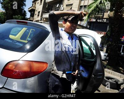 Damascus, Syria. 31st May, 2016. A young Syrian mechanic shields his face from the scorching sun while fixing a - Stock Photo