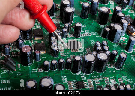 Electronics Repair service close-up with red probe and capacitors on electronic board - Stock Photo