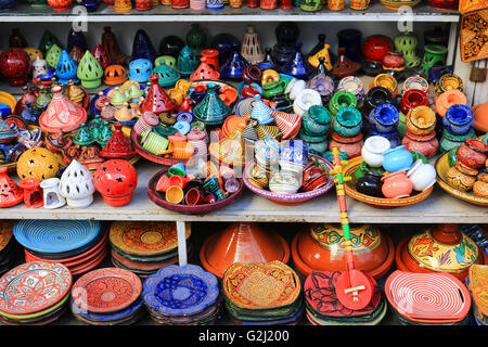 Colorful pottery such as tajines, plates and candle holders for sale on shelves in Morocco - Stock Photo