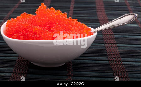 Red caviar in a white bowl on black wooden background with silver spoon - Stock Photo