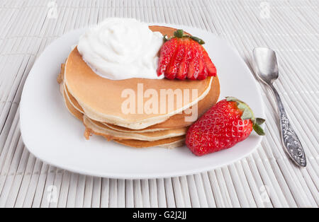 Pancakes on white background with cream  strawberry and silver spoon - Stock Photo