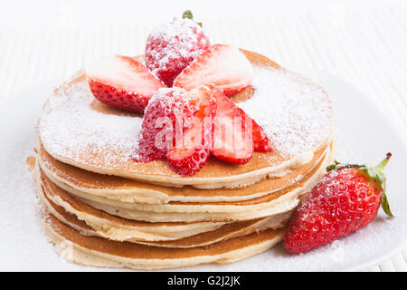 Pancakes on white background with  strawberry and sugar - Stock Photo