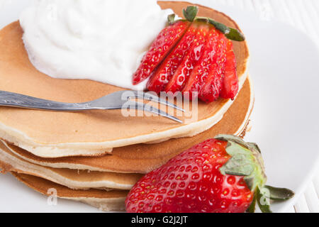Pancakes on white background with cream  strawberry and silver fork - Stock Photo