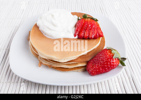 Pancakes on white plate and  background wiyh cream and strawberry - Stock Photo