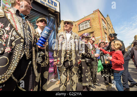 Traditional Pearly Kings and Queens in full costume collecting donations in London on Brick Lane Shoreditch - Stock Photo