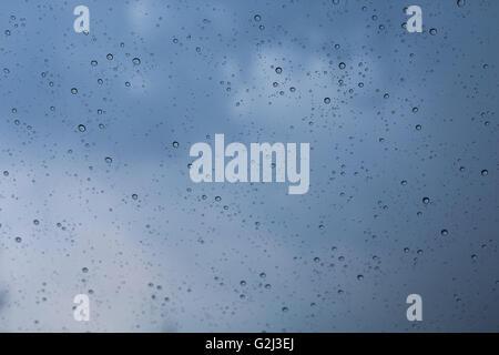 Rain drops on car's windshield in the blue rainy season in rainy city like Seattle, London or tropical equator plentiful - Stock Photo