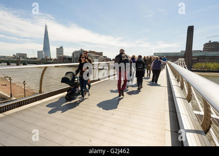 Tourists walking across the famous Millennium bridge in London on May Day Bank Holiday in sunshine towards the Tate - Stock Photo