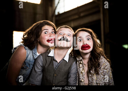 Two Wide-Eyed Girls and Boy Wearing Wax Lips and Making Silly Faces in Abandoned Warehouse - Stock Photo