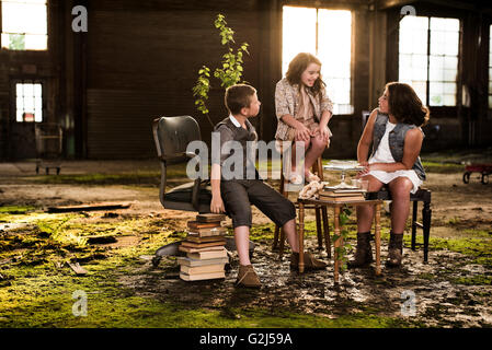 Children Having Tea Party in Abandoned Warehouse - Stock Photo