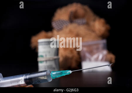 Drug drop syringe closeup with taddy bear in the background - Stock Photo