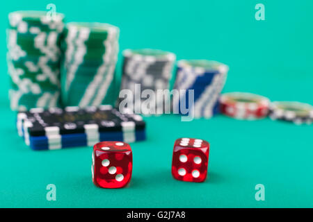 Red pair of dice on green with casino chips in the background - Stock Photo