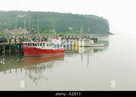 Fishing boats in harbour in fog Alma New Brunswick Canada - Stock Photo