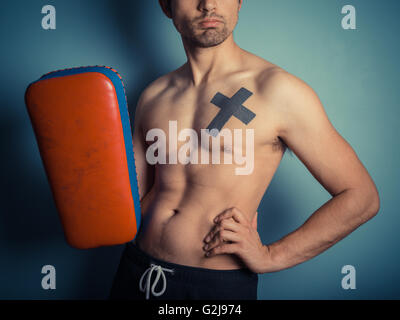 An athletic young shirtless man is holding pads and is ready for some muay thai or mixed martial arts training - Stock Photo