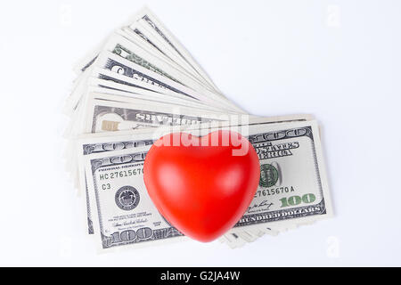 red  heart on top of dollars white background - Stock Photo