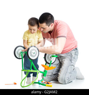 Child boy and daddy fixing bisycle - Stock Photo