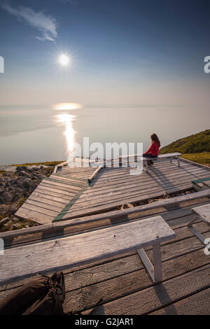 Hiker admires view from Skyline Trail on top of French Mountain in Cape Breton Highlands National Park Nova Scotia - Stock Photo