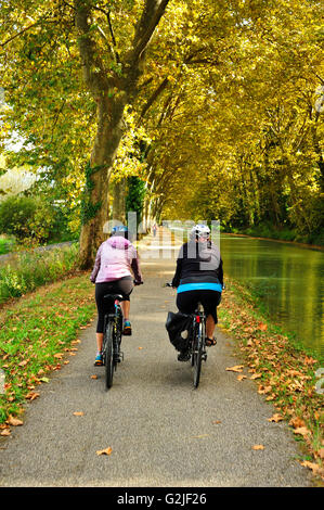 two cyclists on towpath beside the Canal de Garonne near Marmande, Lot-et-Garonne Department, Aquitaine, France - Stock Photo
