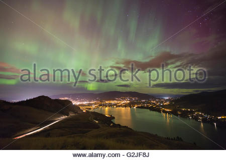 The green pillars of an aurora borealis above the lights of Coldstream and Vernon, North Okanagan, British Columbia, - Stock Photo