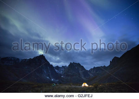 The aurora borealis above Grizzly Lake campground and an illuminated tent, Tombstone Territorial Park, Yukon Territory, - Stock Photo