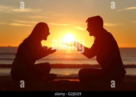 Portrait of a side view of couple or friends silhouette dating and falling in love with a boyfriend giving the sun - Stock Photo