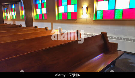 Wooden church pews with stain glass light reflection. - Stock Photo