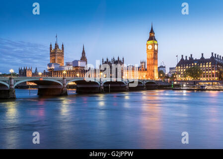 The Houses of Parliament, Big Ben and the River Thames in London, England at dusk - Stock Photo