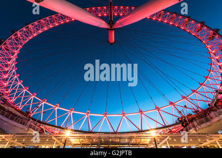 London Eye illuminated in the colour red by its current sponsor Coca Cola - Stock Photo