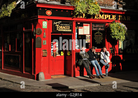 Three men relaxing and telephoning outside The Temple Bar Pub in Dublin during a sunny day, Ireland - Stock Photo