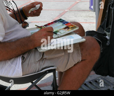 Artist working painting colours concentration fine art clothes to wipe away mistakes, tissues sunglasses around - Stock Photo