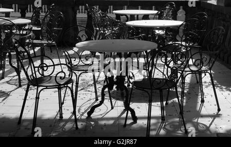 Marble topped tables and cast iron chair on balcony black and white effect - Stock Photo