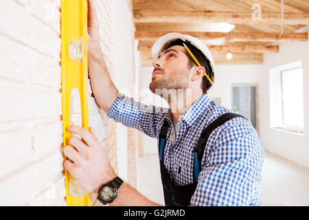 Concentraated builder in uniform holding a level against the wall indoors - Stock Photo